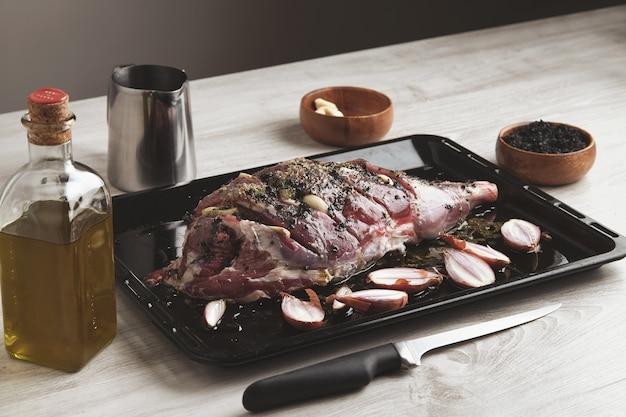 Voorgekookt ijslands lamsboutvlees met specerijen en kruiden en kleine uien op zwarte ovenschaal omringd met keukengerei, olijfoliefles en houten kom met zwart zout en mes vooruit
