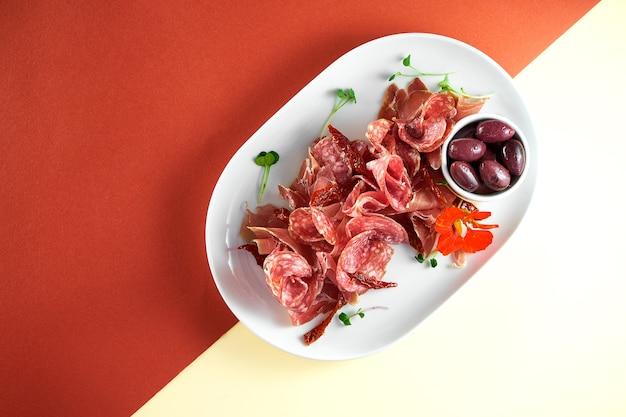 Voorgerecht - antipasti vleesbord met salami, jamon en olijven op felgekleurd oppervlak