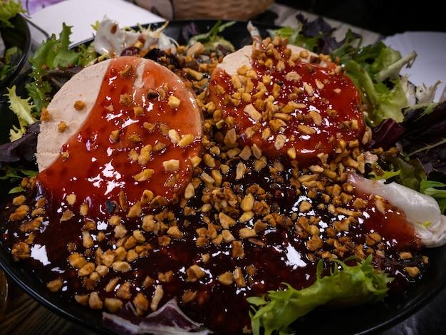 Voorgerecht foie gras gegarneerd met groente. verschillende eendenpastei met kruiden en jam, op het bord op een tafel in een restaurant met decor.
