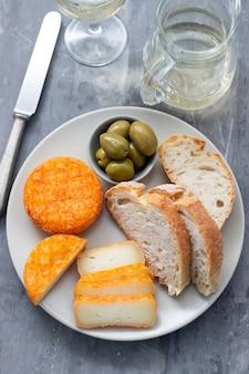 Voorgerecht kaas met brood en olijven op schotel