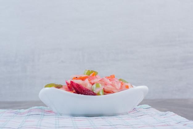 Voorgerecht kom van diverse ingemaakte groenten op tafellaken op marmer.