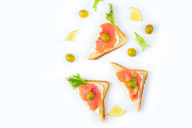 Voorgerecht, open sandwich met zalm en zachte kaas op witte achtergrond. traditionele italiaanse of scandinavische keuken.
