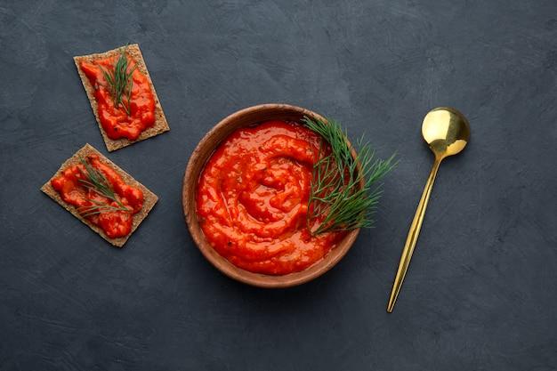 Voorgerecht van ajvar gebakken peper in een kom op een donkere ruimte