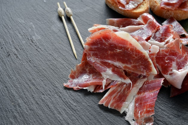 Voorgerecht van ham serrano met geroosterd brood en vergezeld van een glas wijn