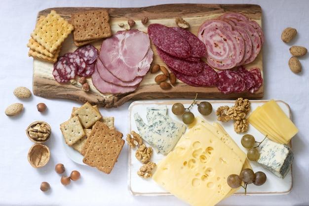 Voorgerecht van verschillende soorten worst, vlees, kaas en crackers op een houten bord, geserveerd aan wijn.