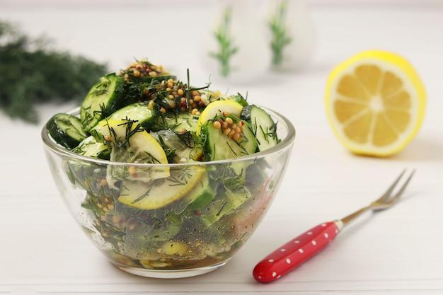 Voorgerecht van verse komkommers met citroen, dille en mosterd bevindt zich in een glazen slakom op wit oppervlak