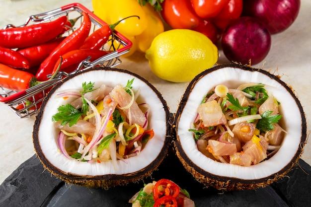 Voorgerecht van verse vis gemarineerd in citrus met tropisch fruit geserveerd in een coconut bowls.