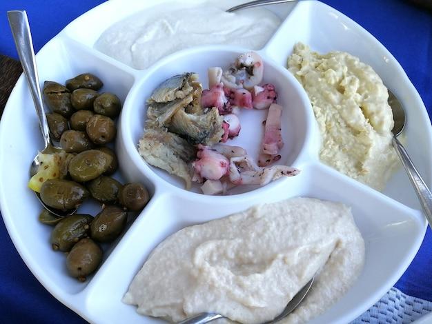 Voorgerecht van zeevruchten, olijven en diverse sauzen van cyprus. tzatziki, taramasalata, tahin