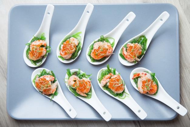 Voorgerecht van zeewierchuka, krabben en kaviaar op geportioneerde spoos. selectieve focus, close-up.