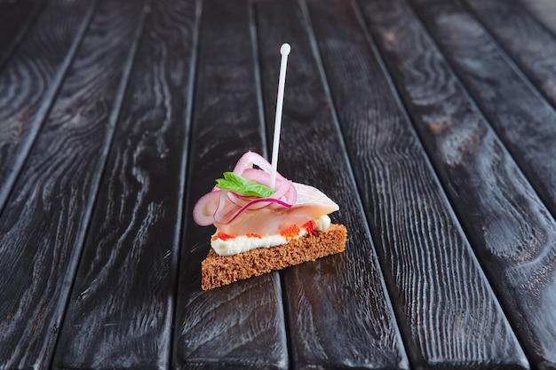 Voorgerecht voor ontvangst. kleine sandwich met haringen, kaas en ui op spies