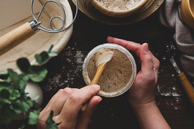 Voorgerecht zuurdesem. vrouwelijke handen met een pot met zuurdesem
