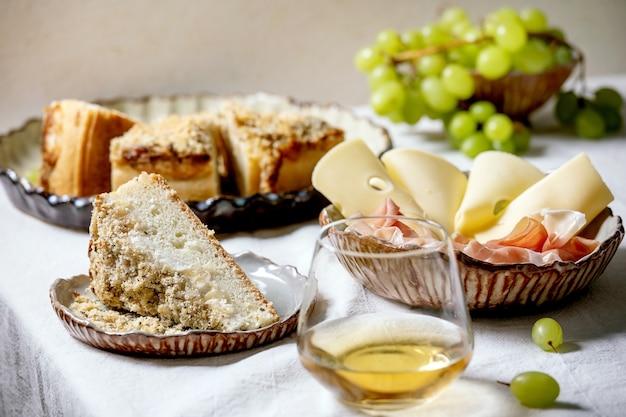 Voorgerechten antipasti met witte siciliaanse focaccia. traditionele brood gesneden cake met ui geserveerd met prosciutto ham, kaas, druiven en glas witte wijn op wit tafelkleed.