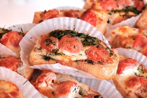 Voorgerechten bruschetta met tomaten en kaas op een feestzaal tafel.