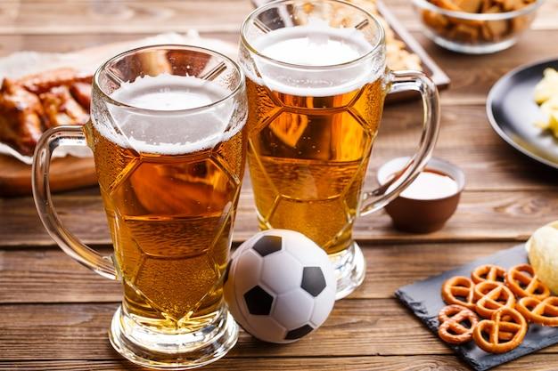 Voorgerechten en bier op tafel om de voetbalwedstrijd te bekijken.