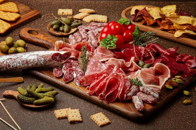 Voorgerechten tafel met verschillende antipasti, kaas, vleeswaren, snacks en wijn. worst, ham, tapas, olijven, kaas en crackers voor buffetfeest.