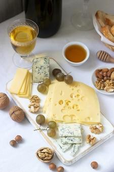 Voorgerechten van verschillende soorten kaas, druiven, noten en honing, geserveerd met witte en rode wijn.