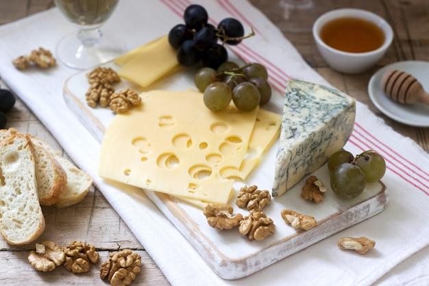 Voorgerechten van verschillende soorten kaas, druiven, noten en honing, geserveerd met witte en rode wijn