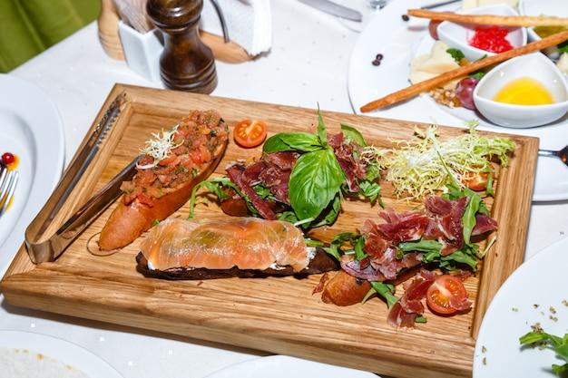 Voorgerechten van zeevruchten en vlees op houten plaat in restaurant