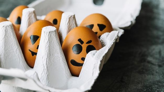 Voorgestelde enge gezichten op eieren die in doos liggen