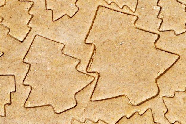 Voorgestelde koekjes snijden in de vorm van een kerstboom