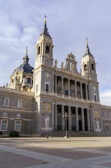 Voorgevel van de almudena-kathedraal in madrid op zonnige dag met wolken. spanje.