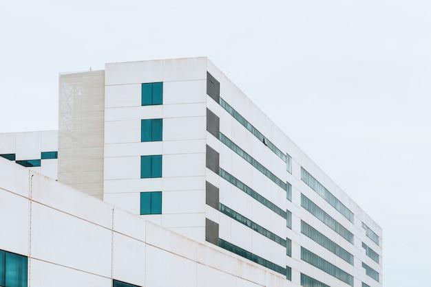 Voorgevel van een wit cement industrieel gebouw met rechte lijnen en hemelachtergrond.