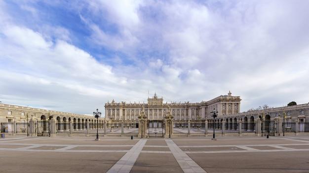 Voorgevel van het koninklijk paleis van madrid met zijn enorme esplanade en blauwe hemel met wolken bij zonsopgang. spanje.