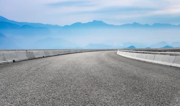 Voorgrond lege weg en verre bergachtergrond
