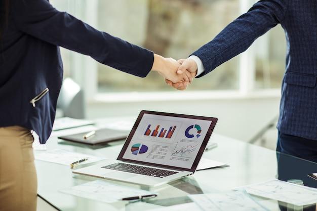 Voorgrond schudt handen met financiële partners in de buurt van de werkplek in het moderne kantoor