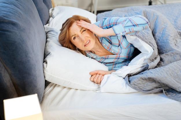 Voorhoofd wrijven. ontevreden vermoeide vrouw die ongelukkig is met het vroege uur terwijl ze onder een dikke deken ligt