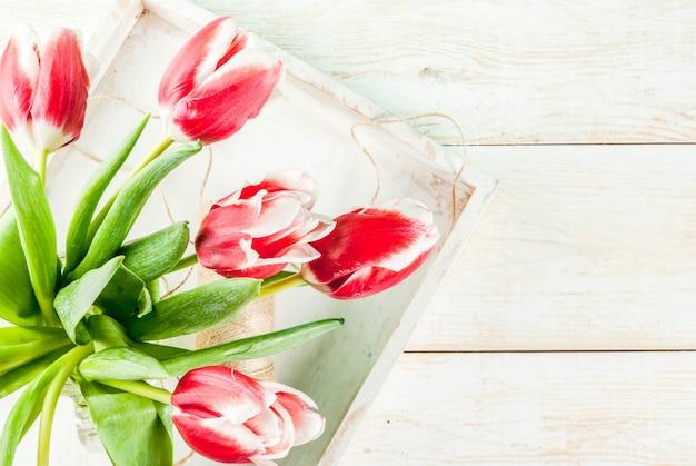 Voorjaar . bloementulpen in een kruik van de glasmetselaar, op houten wit. bovenaanzicht