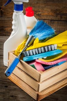 Voorjaarsschoonmaak met benodigdheden, stapel huisreinigingsproducten. het concept van het huishoudenkarwei, op plattelander of houten tuin