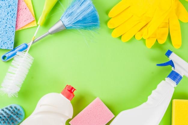 Voorjaarsschoonmaak met benodigdheden, stapel huisreinigingsproducten. huishoudelijke karwei concept, op groen bovenaanzicht frame