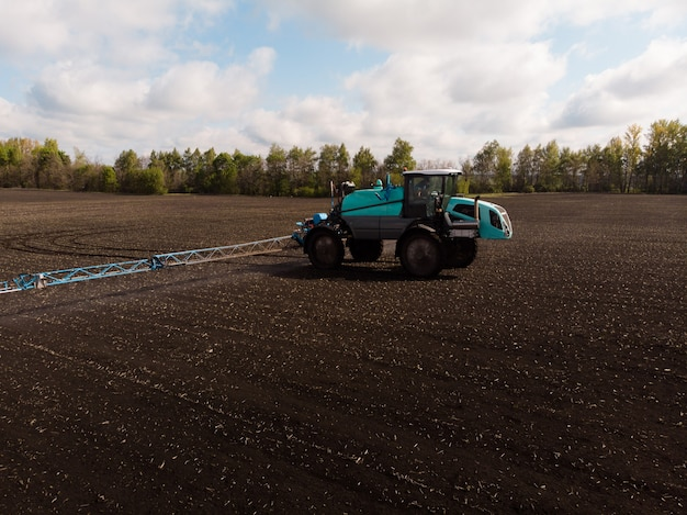 Voorjaarswerk in de landbouw in de velden. de tractor bespuit gewassen met herbiciden, insecticiden en pesticiden.