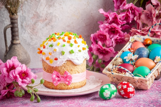 Voorkant close view gekleurde paaseieren in schattige doos met cake op roze oppervlak vakantie kleur kleurrijk concept sierlijke paas lente