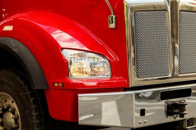 Voorkant van een semi-vrachtwagen terwijl geparkeerde rode vrachtwagen
