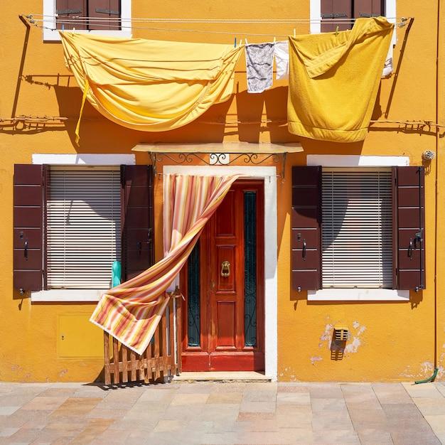Voorkant van het gele huis op het eiland burano. venetië, italië
