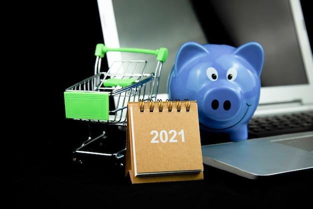 Voorkant van kalender 2021 en miniboodschappenwagentje met blauw spaarvarken op laptop met donkere achtergrond.