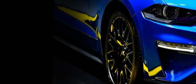 Voorkoplampen van blauwe moderne auto op zwarte achtergrond