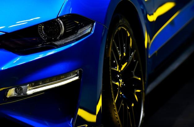 Voorkoplampen van blauwe moderne autoachtergrond