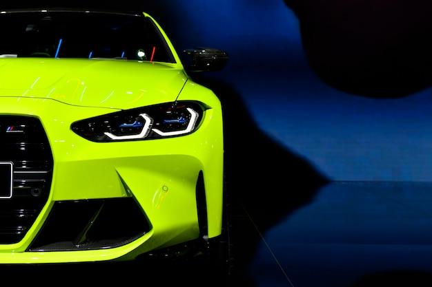 Voorkoplampen van groene moderne sportwagen op zwarte vrije ruimte als achtergrond aan de rechterkant voor tekst