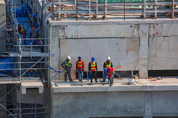 Voorman bouwingenieur doorlopende opdrachten voor arbeidersteam om met hoge veiligheid te werken