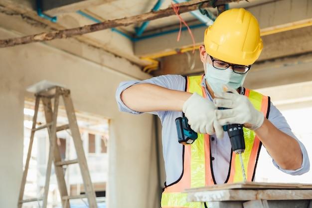 Voorman bouwvakker in veiligheidshelm veiligheidshelm boren door elektrische boor op de bouwplaats. chirurgisch gezichtsmasker dragen tijdens coronavirus covid en griepuitbraak
