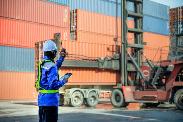 Voorman die walkietalkie gebruikt en praat om het laden van containers naar de vrachtwagen te regelen bij het container depotstation voor logistieke importexport