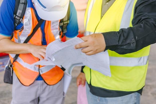 Voorman twee die beschermende kledingsbespreking op een bouwwerf dragen als achtergrond