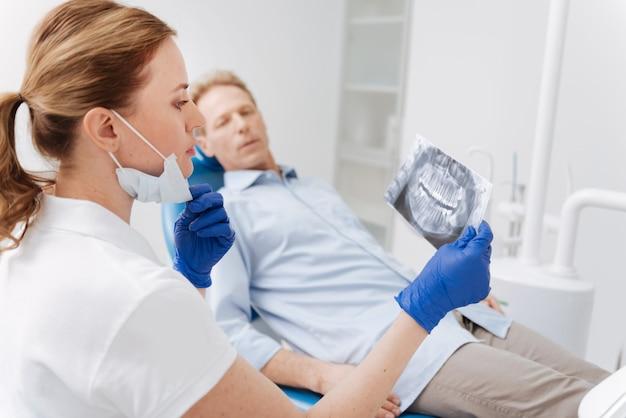 Voorname slimme gerichte arts die de kaakscan van de patiënt onderzoekt en de resultaten analyseert terwijl hij een plan voor zijn behandeling ontwikkelt