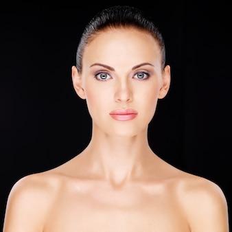 Voorportret van de vrouw met schoonheidsgezicht over zwarte achtergrond