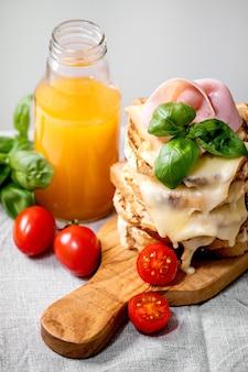 Voorraad van geroosterde gesmolten kaas geperst sandwiches met ham vlees, kerstomaatjes, jus d'orange en basilicum bladeren op houten snijplank op witte marmeren tafel