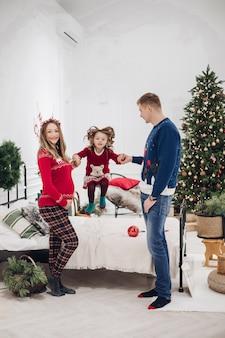 Voorraad volledige lengte foto van vrolijk meisje springen op bed met haar ouders met haar armen. familie in slaapkamer ingericht voor kerstmis.