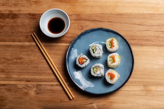Voorraadfoto ok maki-sushi op blauwe plaat, soja en eetstokjes. aziatische gastronomische voedselsamenstelling op houten lijst. makis zalm en groenten.
